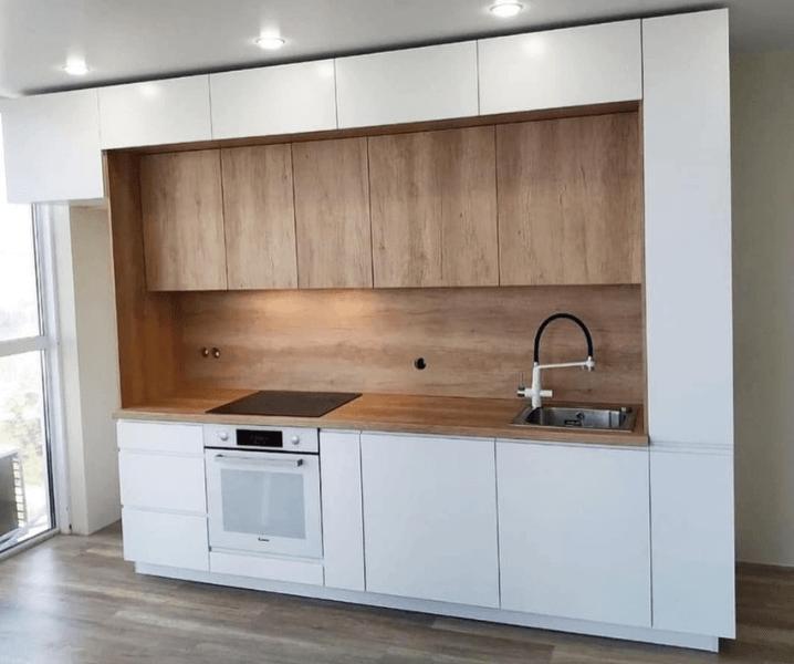 Современная белая кухня с деревянной столешницей с белой плитой