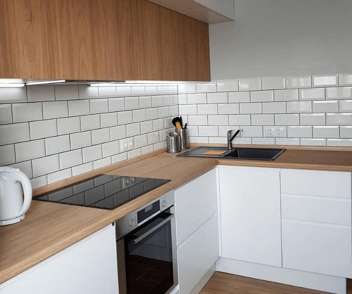 Современная белая кухня с деревянной столешницей с кафелем