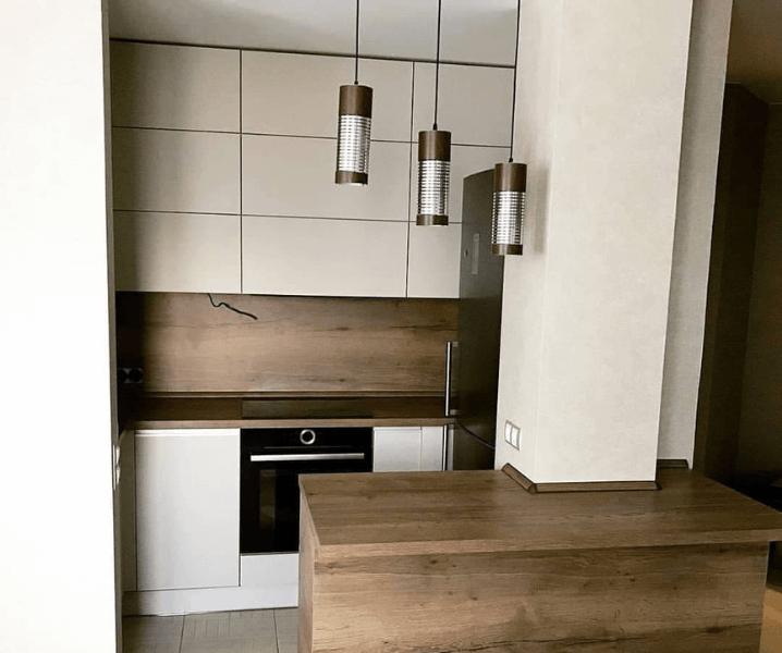 Современная белая кухня с деревянной столешницей дизайнеские светильники