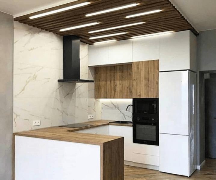 Современная белая кухня с деревянной столешницей с техникой