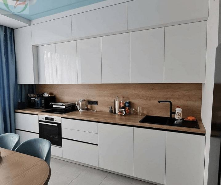 Современная белая кухня с деревянной столешницей черный кран