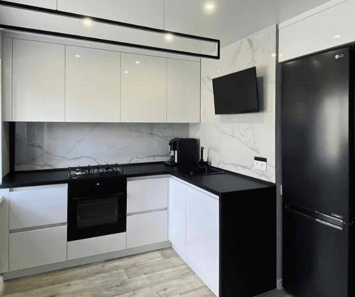 Дизайн угловой кухни в современном стиле белая с черным холодильником